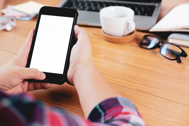 Zbliżenie ręki używać smartphone przy biurowym biurkiem. Premium Zdjęcia