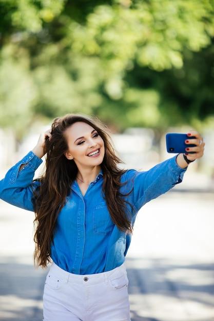 Zbliżenie Selfie Portret Student Atrakcyjna Dziewczyna W Okularach Przeciwsłonecznych Z Długą Fryzurą I śnieżnobiałym Uśmiechem W Mieście. Darmowe Zdjęcia
