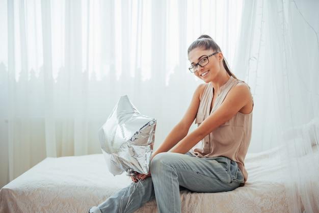 Zbliżenie śliczna brunetki dziewczyna uśmiecha się szeroko i bawić się z balonami przejrzystymi i srebnymi. nosi okulary i kręcone włosy. Premium Zdjęcia