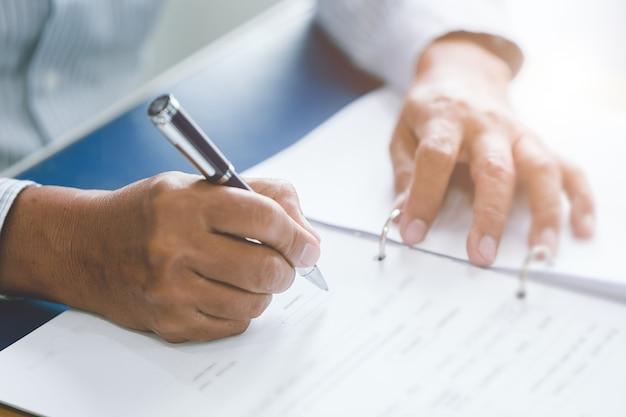 Zbliżenie Starszy Ręka Papier Do Pisania Pracy Z Długopisem W Biurku. Premium Zdjęcia