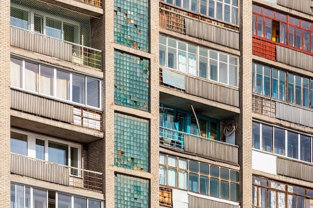 Zbliżenie starych przeszklonych balkonów wielopiętrowego domu panelowego w części sypialnej. fasada starego domu Premium Zdjęcia