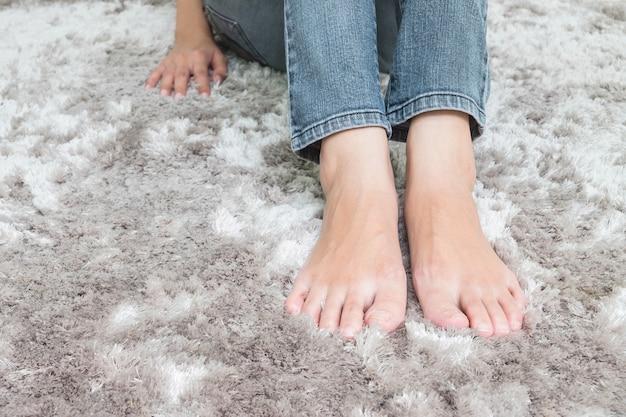 Zbliżenie stopy azjatykci kobiety obsiadanie na szarej dywanowej podłoga textured tło w domu Premium Zdjęcia
