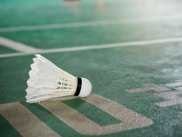 Zbliżenie strzelający biały badminton shuttlecock na zieleń sądzie. Premium Zdjęcia