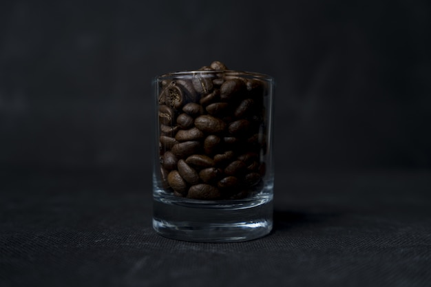 Zbliżenie Strzelał Szkło Kawowe Fasole Na Ciemnej Powierzchni Darmowe Zdjęcia