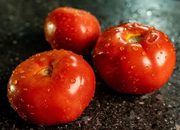 Zbliżenie świeżych Dojrzałych Pomidorów Z Kroplami Wody Na Powierzchni Blatu Kuchni Czarnego Granitu Darmowe Zdjęcia
