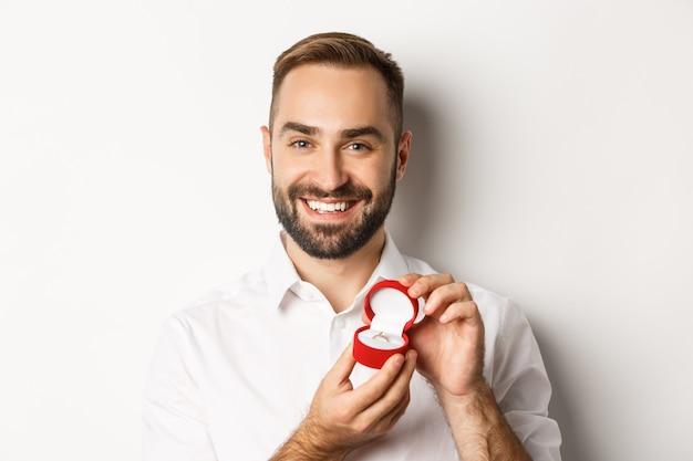 Zbliżenie: Szczęśliwy Przystojny Mężczyzna Składający Propozycję, Trzymając Obrączkę W Pudełku I Uśmiechnięty, Prosząc O Poślubienie Go Darmowe Zdjęcia