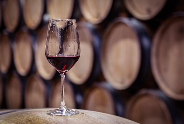 Zbliżenie szkło z czerwonego wina na drewnianej beczce dębowej wina ułożone w prostych rzędach w kolejności, stara piwnica winnicy, sklepienie. profesjonalna degustacja, winelover, sommelier travel Premium Zdjęcia