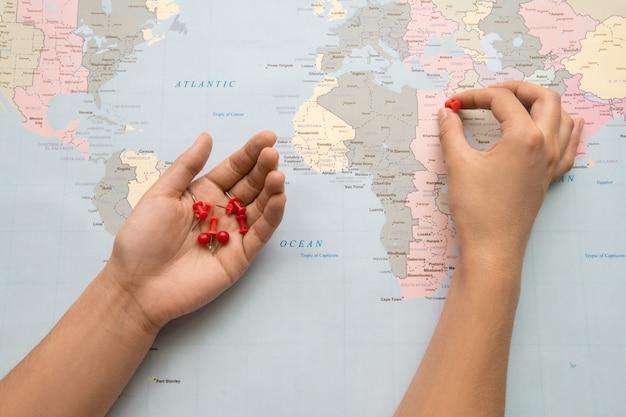 Zbliżenie Turysty Stawiając Czerwone Szpilki Na Papierowej Mapie Podczas Tworzenia Miejsca Do Odwiedzenia Premium Zdjęcia