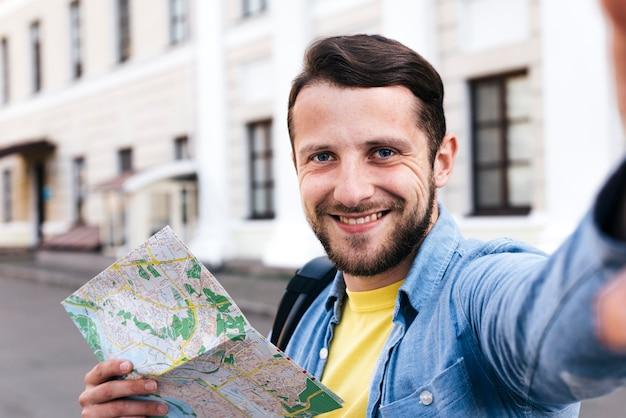 Zbliżenie: uśmiechnięty mężczyzna trzyma mapę przy selfie w plenerze Darmowe Zdjęcia