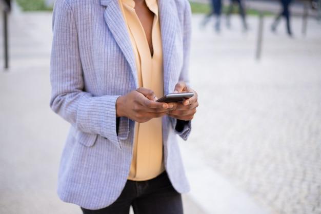 Zbliżenie Widok Kobiet Ręki Używać Nowożytnego Telefon Na Ulicie Darmowe Zdjęcia