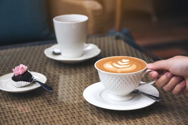 Zbliżenie Wizerunek Ręka Trzyma Filiżankę Gorąca Latte Kawa Z Latte Sztuką I Przekąską Premium Zdjęcia