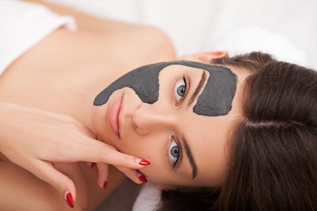 Zbliżenie zdjęcie pięknej młodej kobiety z maską śmietany w salonie piękności. Premium Zdjęcia