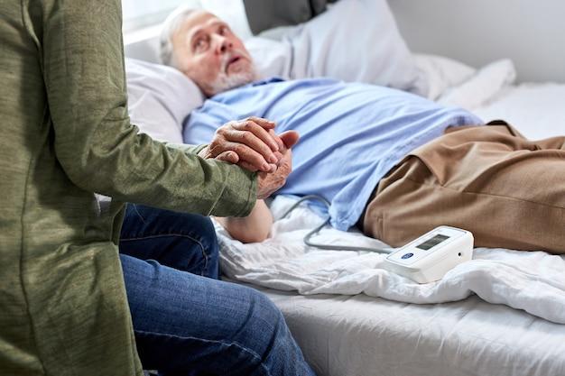 Zbliżenie Zdjęcie Senior Para Trzymając Się Za Ręce Razem, Kobieta Wspiera Swojego Chorego Męża Leżącego Na łóżku W Szpitalu Premium Zdjęcia