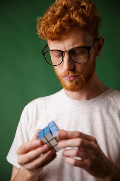 Zbliżenie Zdjęcie Skoncentrowanego Faceta W Okularach, Bawiącego Się Kostką Rubika Darmowe Zdjęcia