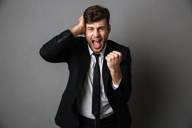 Zbliżenie Zdjęcie Zły Krzyczący Młody Człowiek W Czarnym Garniturze, Obejmujące Jego Ucho I Zaciskając Pięści Darmowe Zdjęcia