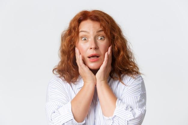 Zbliżenie Zdziwionej I Szczęśliwej, ślicznej Rudowłosej Kobiety W średnim Wieku Dotykającej Policzków Premium Zdjęcia