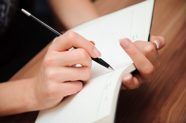 Zbliżenie żeński ręki writing na pustym notatniku z piórem Premium Zdjęcia