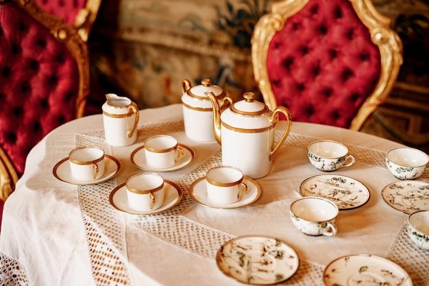 Zbliżenie: Zestawy Herbaty Na Białym Koronkowym Obrusie Z Pluszowymi Czerwonymi Krzesłami Premium Zdjęcia