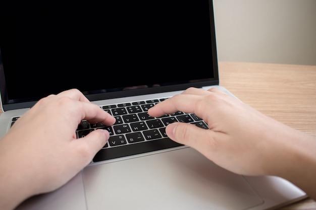 Zbliżone zdjęcia dłoni, które poważnie pracują na laptopach. Premium Zdjęcia