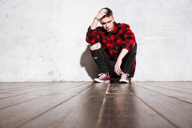 Zbuntowany Mężczyzna W Kraciastej Koszuli, Pozowanie, Siedząc Przy ścianie Darmowe Zdjęcia