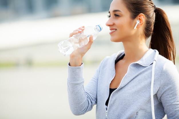 Zdatność. piękna kobiety woda pitna i słucha muzyka po biegać Premium Zdjęcia