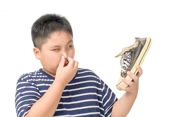 Zdegustowany Gruby Chłopak Trzymający Parę śmierdzących Butów Premium Zdjęcia