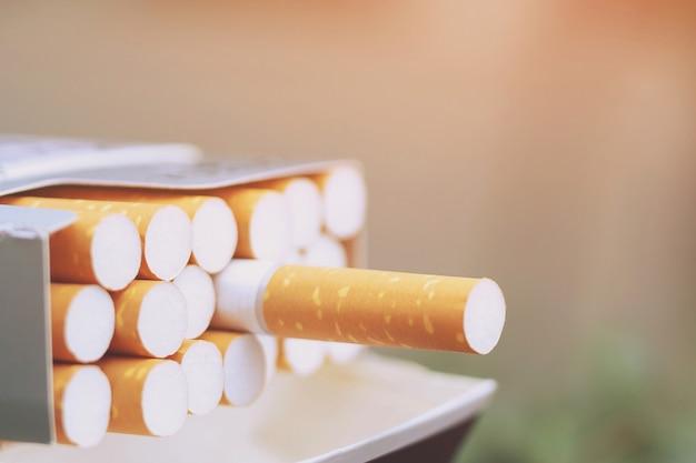 Zdejmij z niego opakowanie papierosów przygotuj palenie papierosa. linia pakująca. Premium Zdjęcia