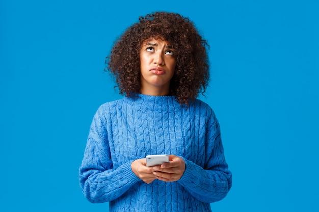 Zdenerwowana I Niespokojna Afroamerykańska Ponura Dziewczyna Czuje Się Jak Przegrana, Patrząc W Niebo Pytając Boga Dlaczego, Wzdychając Smutno, Trzymając Smartfon, Stojąc Niespokojnie I Dąsając Się Na Niebiesko Premium Zdjęcia