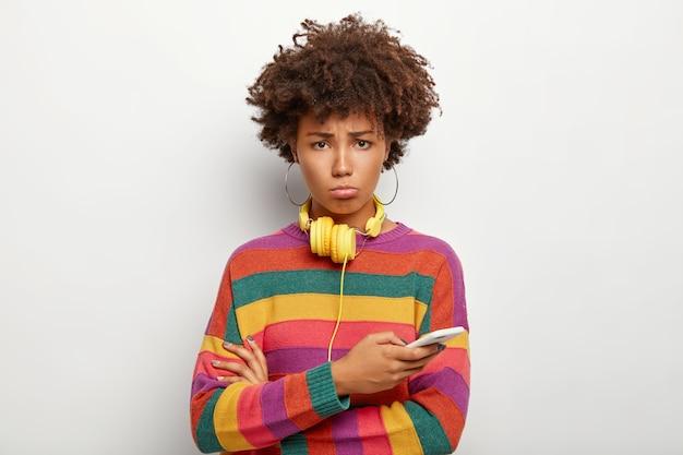 Zdenerwowana Kręcona Afro Kobieta O Smutnym Wyglądzie, Używa Telefonu Komórkowego, Nie Może Wypłacić Pieniędzy Z Konta Internetowego, Używa Słuchawek Do Słuchania Muzyki Darmowe Zdjęcia