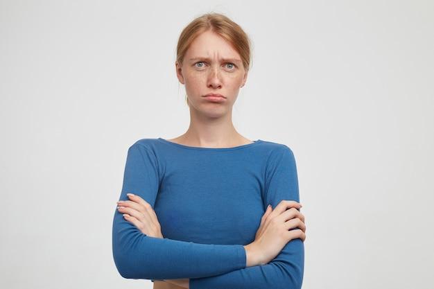 Zdenerwowana Młoda Atrakcyjna Kobieta Z Przypadkową Fryzurą Krzyżującą Dłonie Na Piersi, Pozując Na Białym Tle, Marszcząc Brwi I Składając Usta, Patrząc Na Kamery Darmowe Zdjęcia