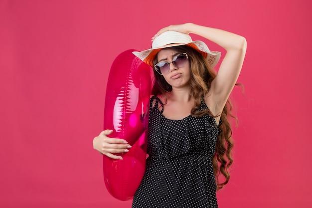 Zdenerwowana Młoda Piękna Podróżniczka W Sukience W Kropki W Letnim Kapeluszu W Okularach Przeciwsłonecznych Trzymająca Nadmuchiwany Pierścień Patrząc Na Kamery Ze Smutnym Wyrazem Twarzy Stojącej Na Różowym Tle Darmowe Zdjęcia