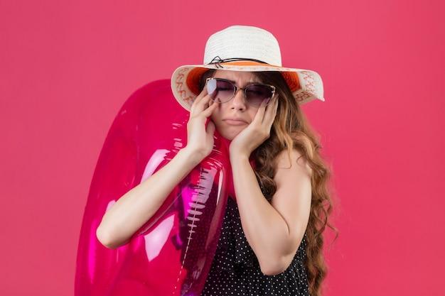 Zdenerwowana Młoda Piękna Podróżniczka W Sukience W Kropki W Letnim Kapeluszu W Okularach Przeciwsłonecznych Trzymająca Nadmuchiwany Pierścionek Ze Smutnym Wyrazem Twarzy Na Różowym Tle Darmowe Zdjęcia