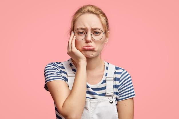 Zdenerwowana Smutna Kobieta żałuje Kłótni Z Bliską Osobą, Zaciska Dolną Wargę, Ma Zdrową Skórę, Blond Włosy, Nosi Casualową Koszulkę Darmowe Zdjęcia