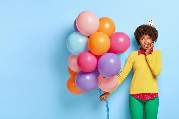 Zdenerwowana, Zaintrygowana Kobieta, Pozując W żółtym Swetrze, Trzyma Wielokolorowe Balony Darmowe Zdjęcia