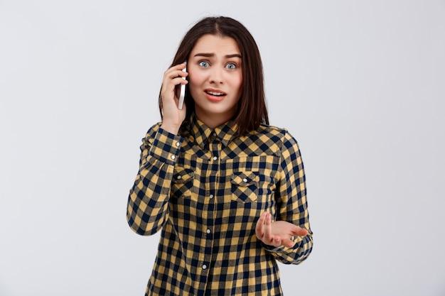 Zdenerwowany Młoda Piękna Dziewczyna Ubrana W Kraciastą Koszulę Mówiąc Na Telefon, Na Białej ścianie. Darmowe Zdjęcia