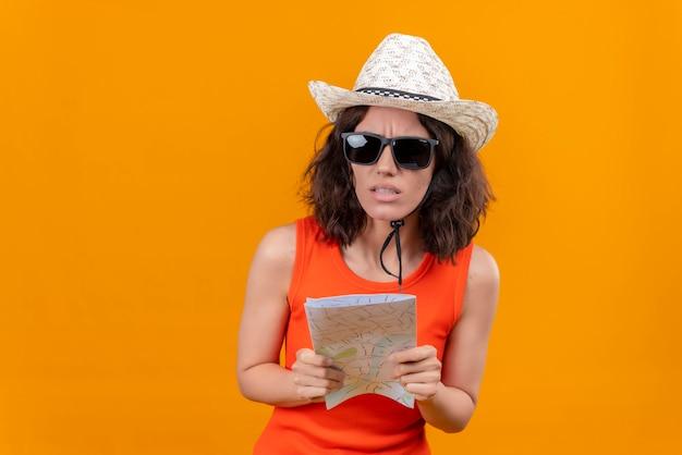 Zdezorientowana Młoda Kobieta Z Krótkimi Włosami W Pomarańczowej Koszuli W Kapeluszu Przeciwsłonecznym I Okularach Przeciwsłonecznych, Trzymając Mapę Darmowe Zdjęcia