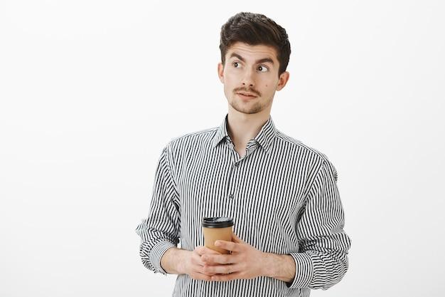 Zdezorientowany Dojrzały Europejski Chłopak Z Wąsami I Brodą, Odwracający Wzrok Z Uniesionymi Brwiami, Pijący Kawę I Przesłuchiwany Zachowaniem Przyjaciela, Myślący, że Jest Dziwny Przez Szarą ścianę Darmowe Zdjęcia