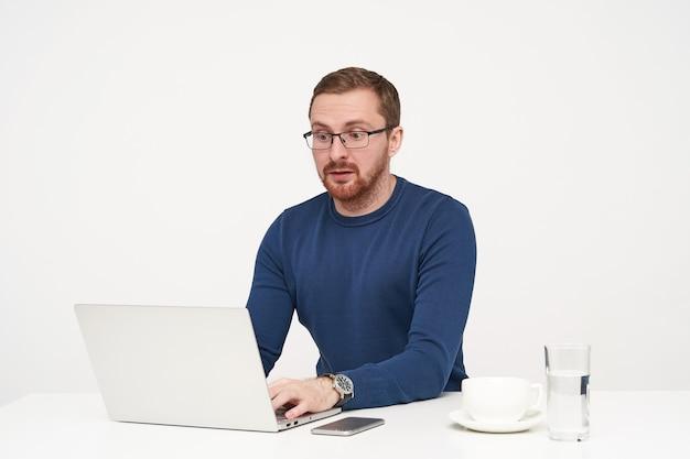 Zdezorientowany Młody Jasnowłosy Mężczyzna W Okularach Trzymający Ręce Na Klawiaturze I Patrząc Zaskoczony Na Ekran Swojego Laptopa, Siedząc Na Białym Tle Darmowe Zdjęcia