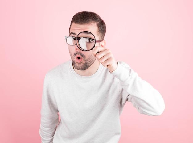 Zdezorientowany Wyraz Młody Człowiek Trzyma Szkło Powiększające W Oku. Ciekawa I Przystojna Twarz Młodego Człowieka. Premium Zdjęcia