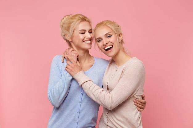 Zdjęcia Dwóch Sióstr, Przytulcie Się I Trzymajcie Się Za Ręce: Cieszę Się, że Mają Się Nawzajem - Zawsze Są Razem Zabawni! Uśmiechy Szeroko Rozjaśniają Się Na Różowym Tle. Darmowe Zdjęcia