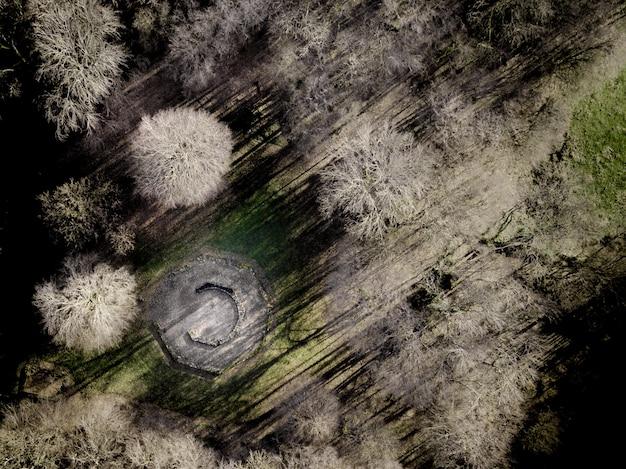 Zdjęcia Lotnicze Z Kominkiem W Otoczeniu Bezlistnych Drzew Na Trawiastym Polu W Ciągu Dnia Darmowe Zdjęcia