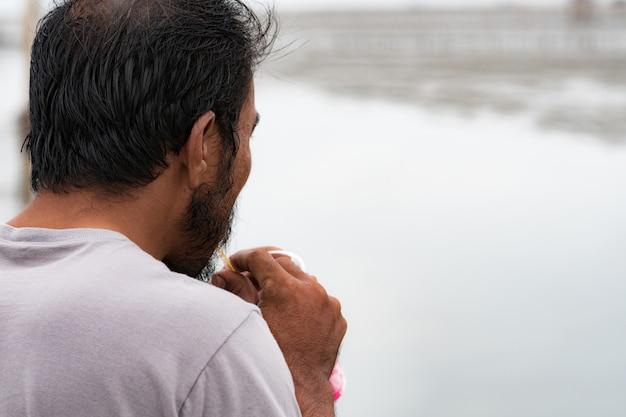 Zdjęcia Z Tyłu, Krótkowłosy Mężczyzna Z Brodą, Pijący Napoje Bezalkoholowe Nad Morzem Premium Zdjęcia
