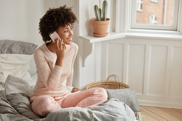 Zdjęcie Afroamerykanki Umawia Się Na Wizytę Przez Komórkę, Ubrana W Zwykłe Ciuchy, Siedzi W Pozycji Lotosu Na łóżku, Nosi Zwykłe Ubrania, Lubi Rozmowę Z Przyjaciółmi, Ma Dzień Wolny, Pozuje W Sypialni Darmowe Zdjęcia