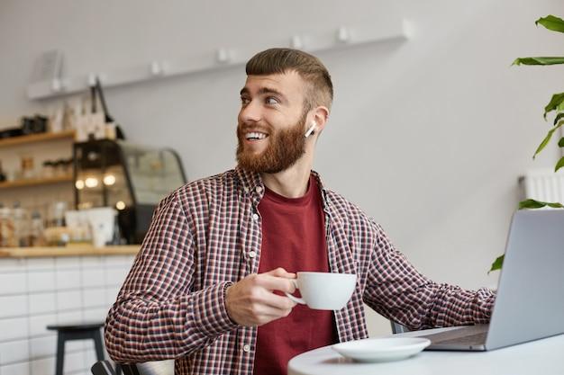 Zdjęcie Atrakcyjnego, Rudego Brodatego Mężczyzny Pracującego Przy Laptopie, Siedzącego W Kawiarni, Pijącego Kawę, Noszącego Podstawowe Ciuchy, Spoglądającego Wstecz, Dzięki Barista Za Wspaniałą Kawę. Darmowe Zdjęcia
