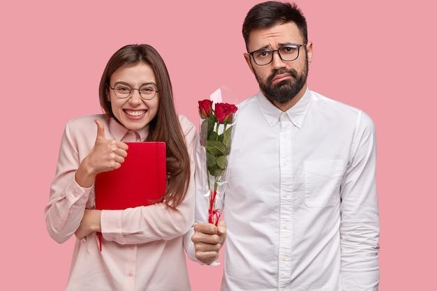 Zdjęcie Atrakcyjnej Kobiety Pokazuje Gest Aprobaty, Trzyma Kciuk, Nosi Czerwony Notatnik, Zdziwiony Nieogolony Mężczyzna Trzyma Bukiet Róż Darmowe Zdjęcia