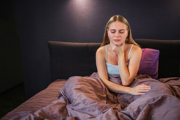Zdjęcie Blondynki Siedzi Na łóżku I Trzyma Jedną Rękę Na Gardle. Ma Tam Ból. Model Ma Zamknięte Oczy. Ona Jest Sama W Pokoju. Premium Zdjęcia
