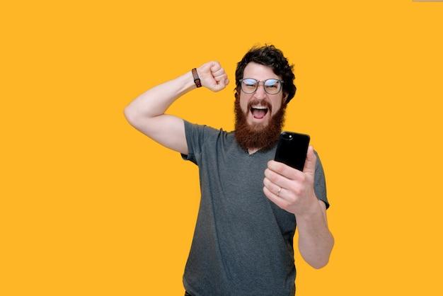Zdjęcie Brodata Faceta Holującego Mobioe I świętującego Z Podniesioną Ręką Na żółto Premium Zdjęcia