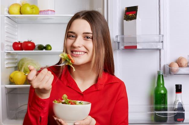 Zdjęcie Dobrze Wyglądającej Młodej Kobiety O Przyjemnym Wyglądzie Stoi W Pobliżu Otwartej Lodówki Z Miską Sałatek, Je Tylko Zdrowe Jedzenie, Będąc W Dobrym Nastroju. Ludzie, Jedzenie, Weganie I Styl życia Premium Zdjęcia
