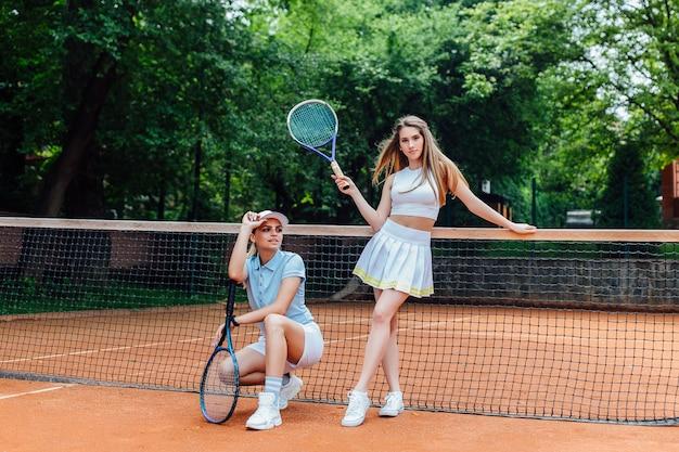 Zdjęcie dwóch tenisistek ze sportowymi dziewczynami z rakietami przygotowanymi do zawodów. Premium Zdjęcia
