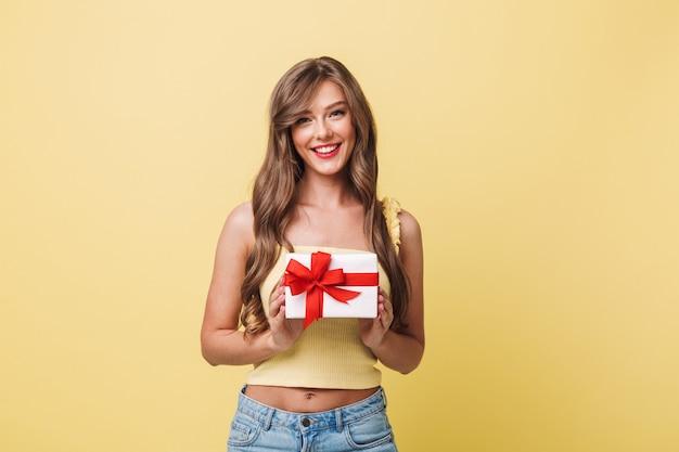 Zdjęcie Kaukaskiej Zadowolonej Kobiety Dwudziestki O Długich Brązowych Włosach, Uśmiechniętej I Trzymającej Pudełko Owinięte Kokardą, Odizolowane Na żółtym Tle Premium Zdjęcia